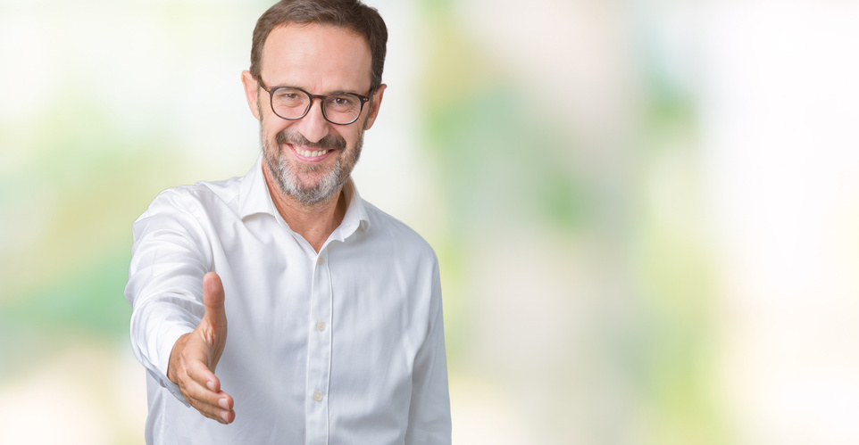 Handsome middle age elegant senior business man wearing glasses over isolated background smiling friendly offering handshake as greeting and welcoming. Successful business.